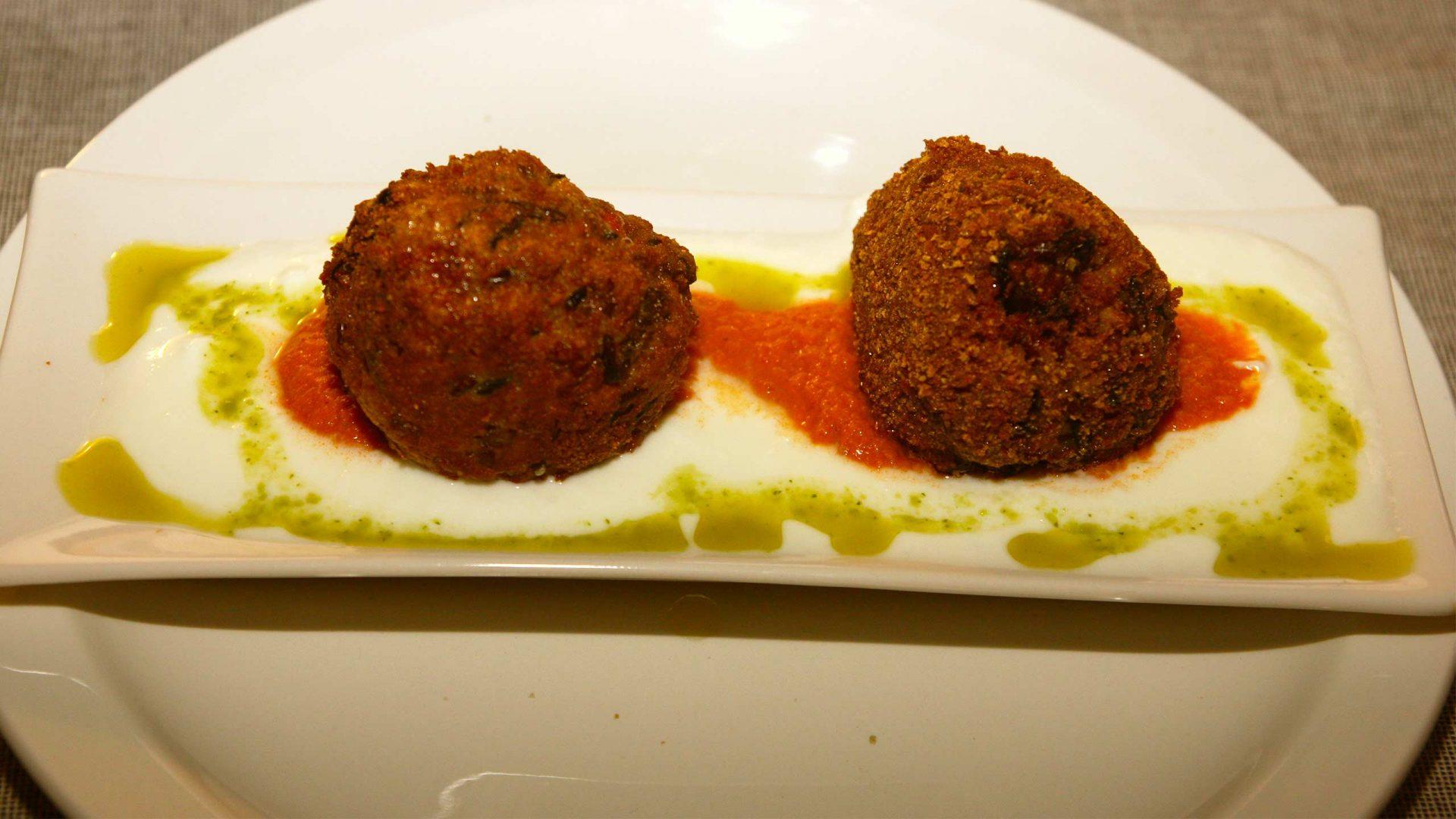 כדורי ריזוטו ממולאים בחלומי שקדים וצימוקים על קונפי עגבניות צלויות ויוגורט